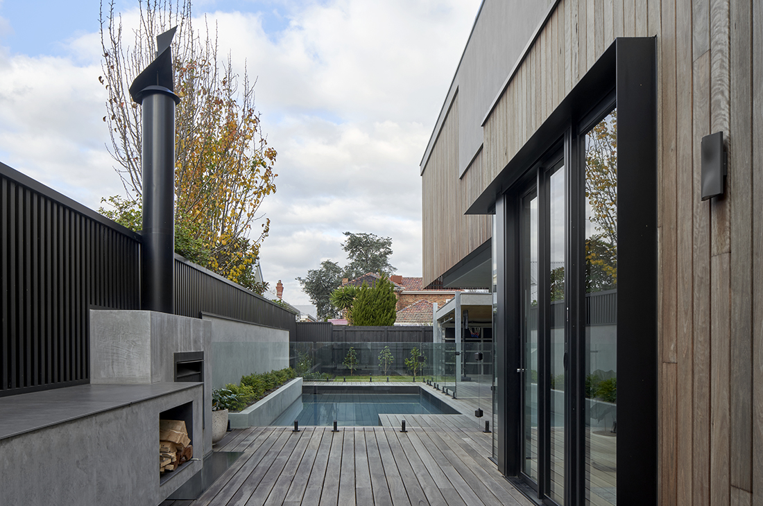 outdoor entertaining space with fireplace shiplap cladding pool