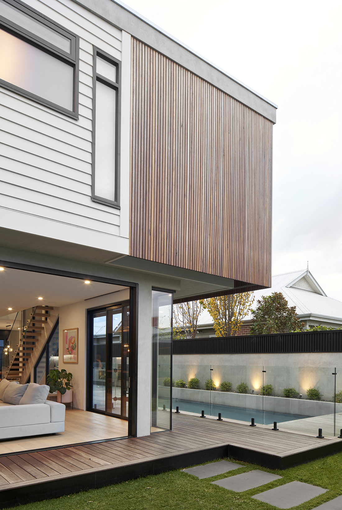contemporary exterior with timber batten and concrete render overlooking pool