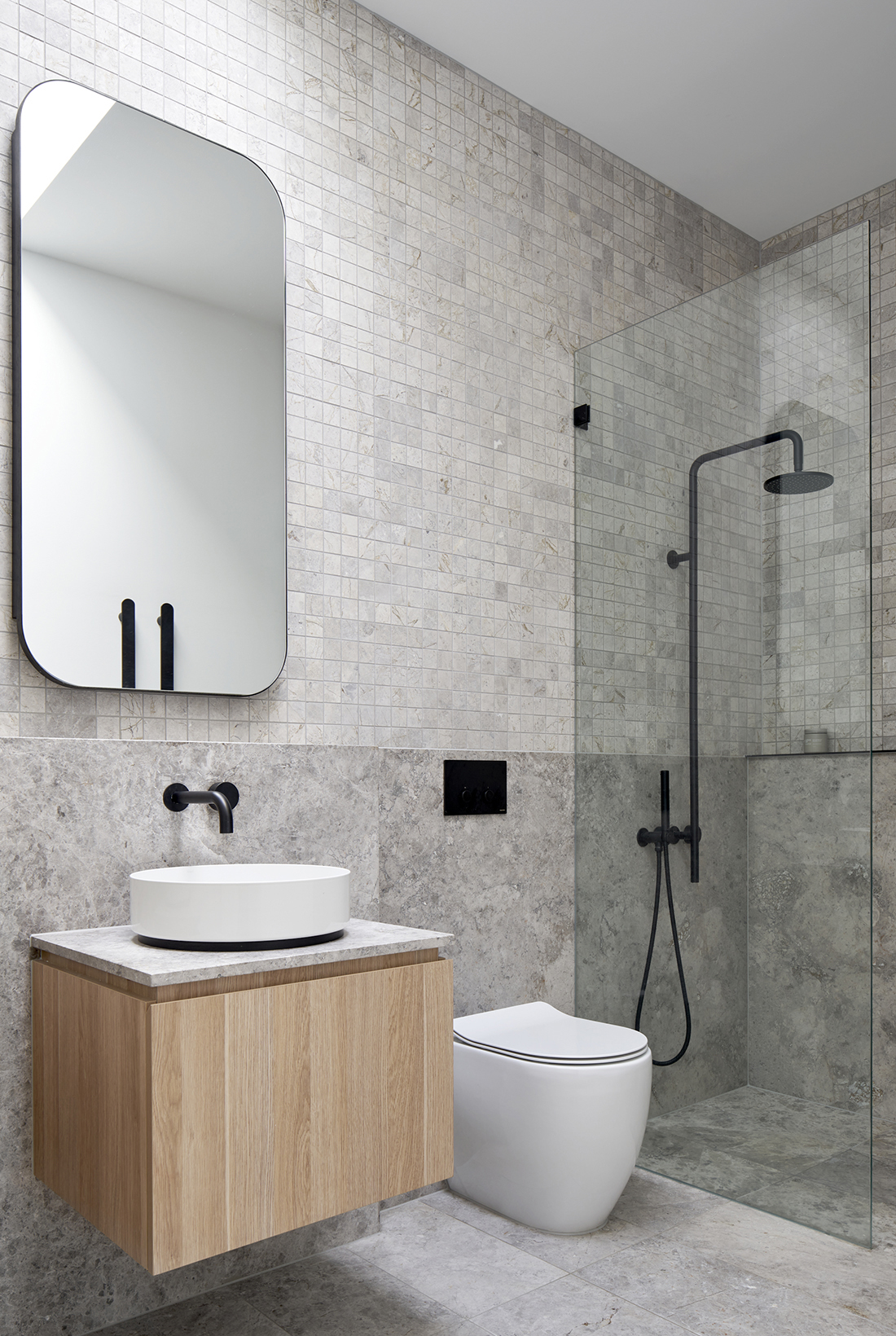 ensuite with natural stone tiles and black tapware