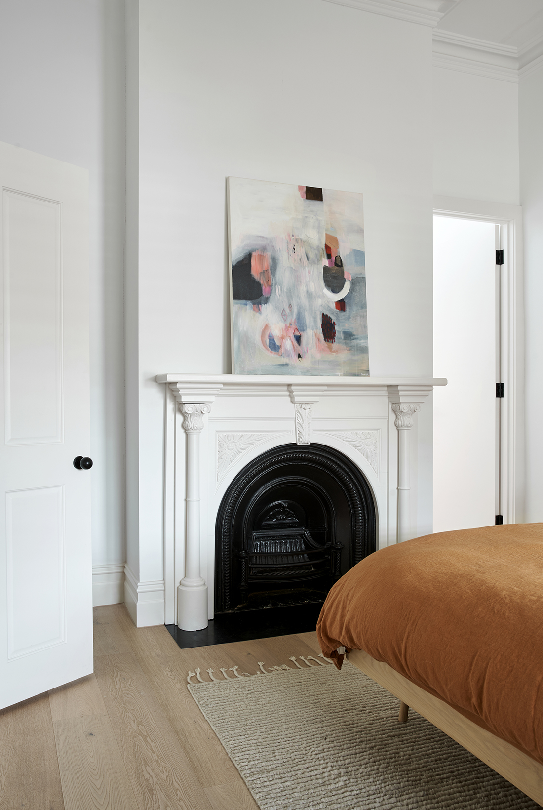 master bedroom with white mantle and black steel hearth