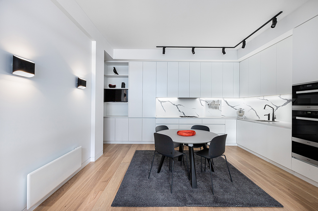 contemporary apartment kitchen white with grande statuario splashbackand miele appliances