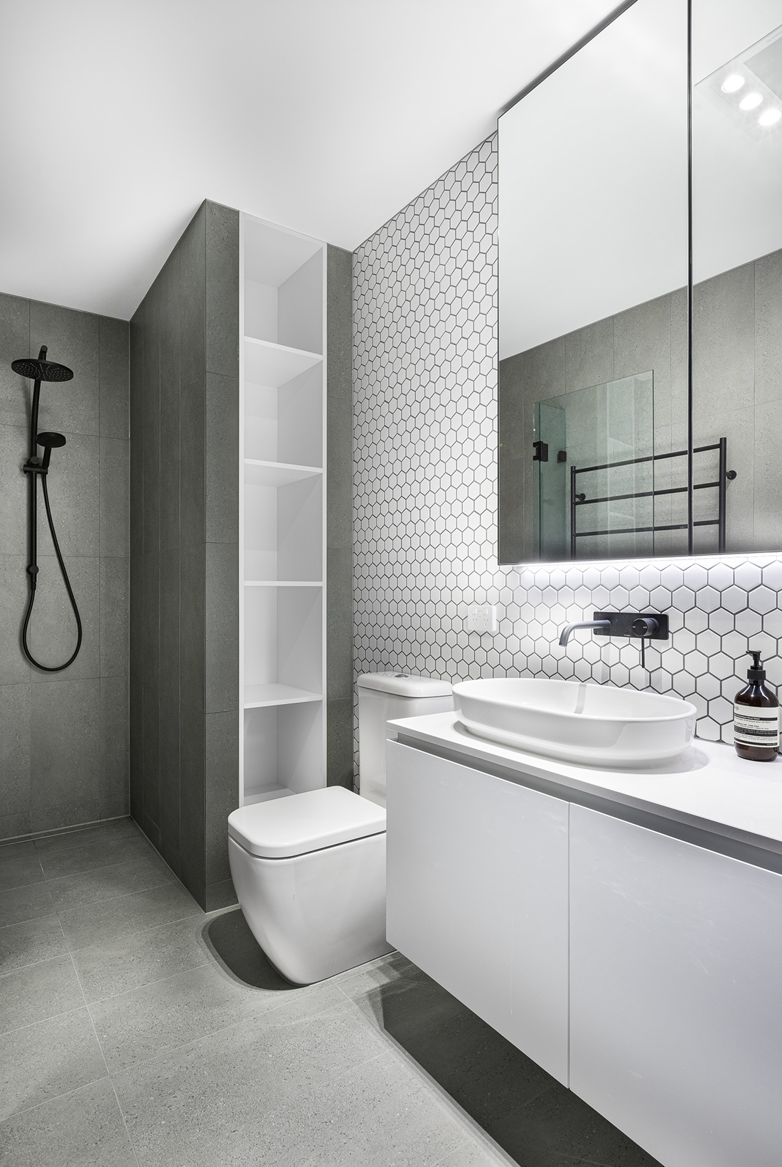 contemporary apartment within heritage building ensuite with hexagon feature tiles and black fixtures