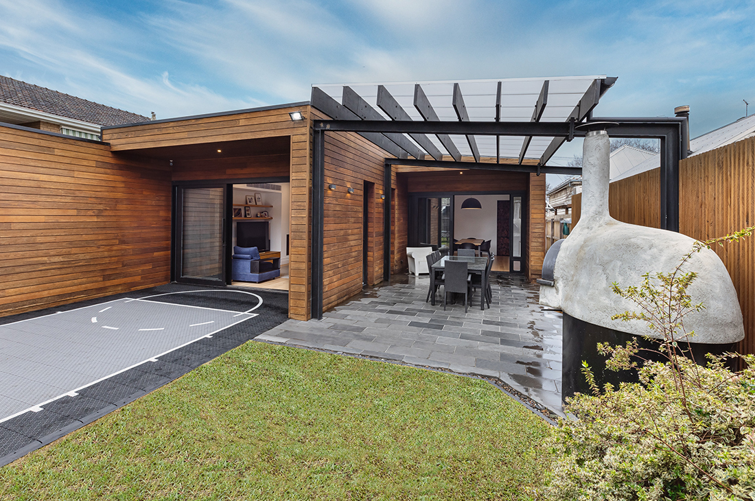 outdoor entertaining space with stonefire pizza oven, shiplap cladding and basketball court