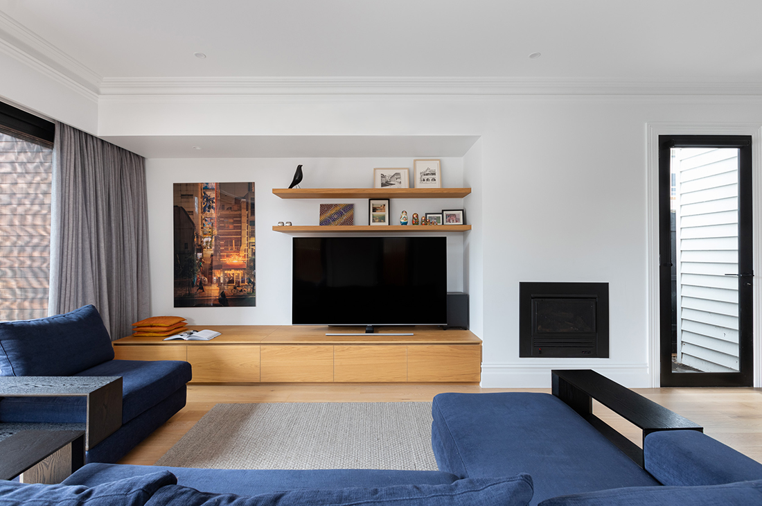 living room with entertainment unit and floating shelves