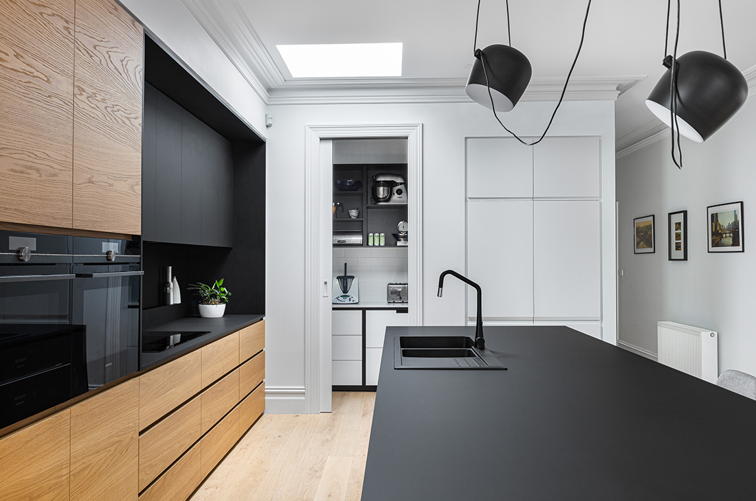 contemporary kitchen with black nanoparticle surface, oak veneer and view into pantry