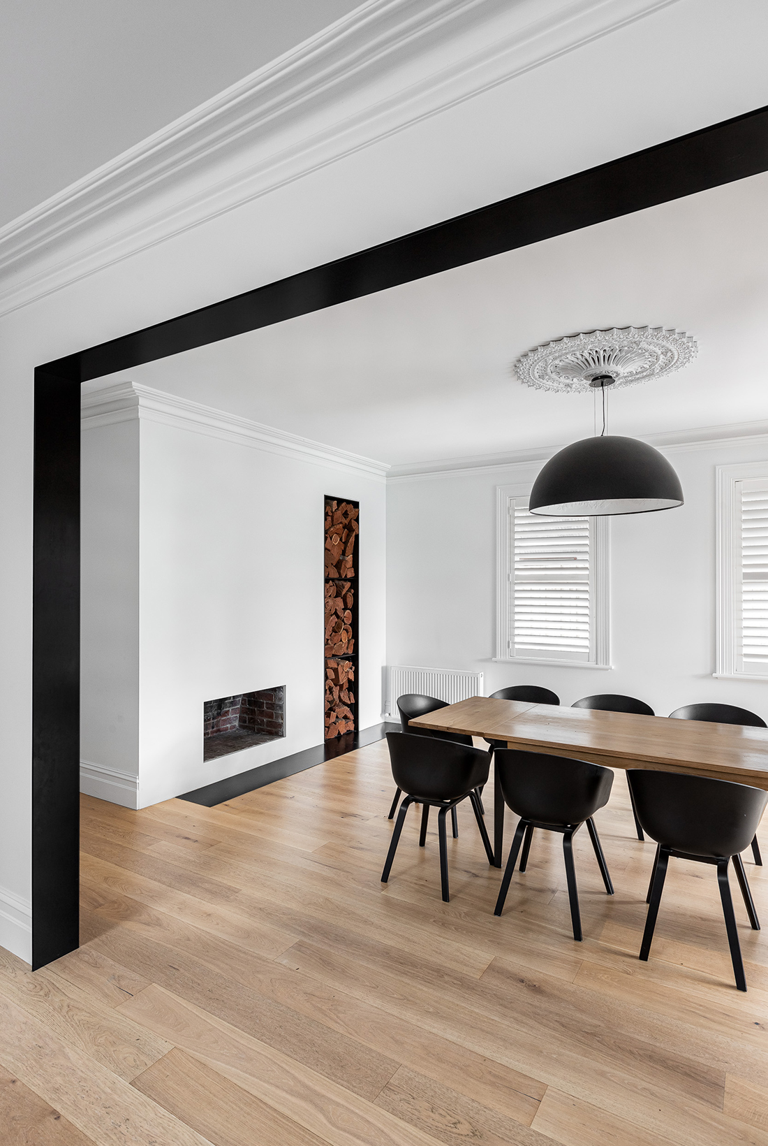 contemporary black steel transition arch into dining room