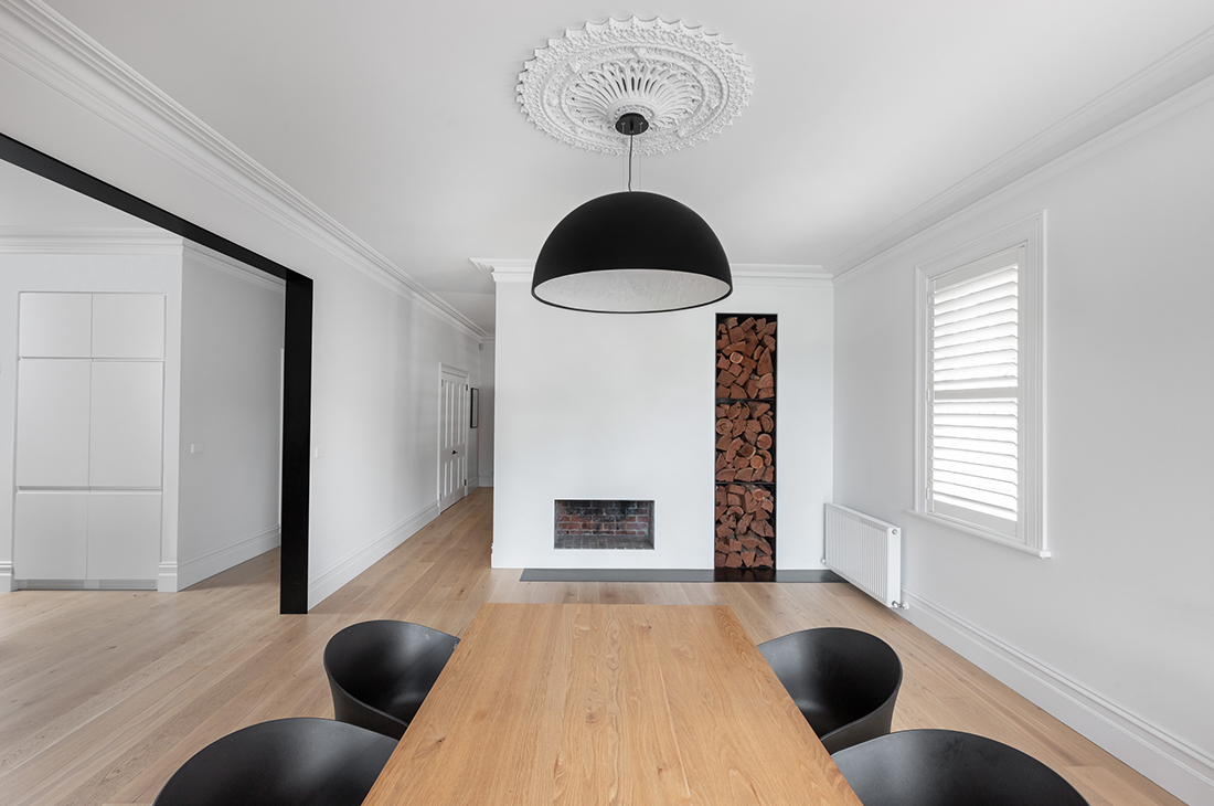 dining room with contemporary black steel transition arch into kitchen, black steel hearth and wood box