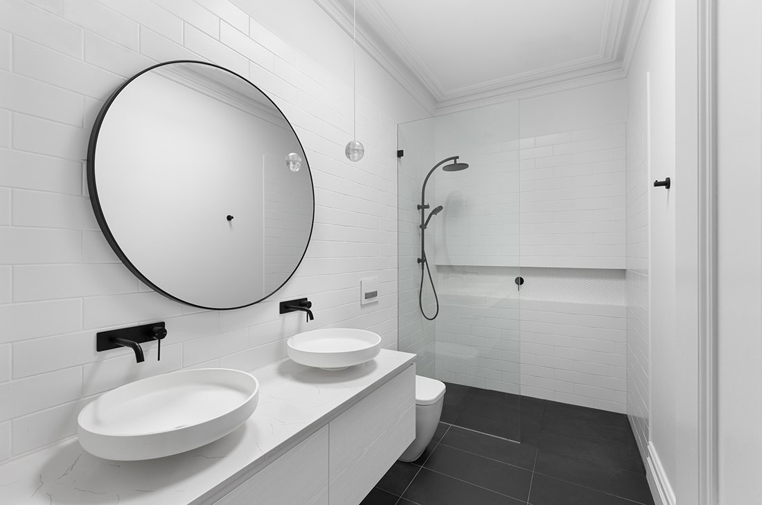 contemporary ensuite with white fixtures, black taps and frameless glass screen