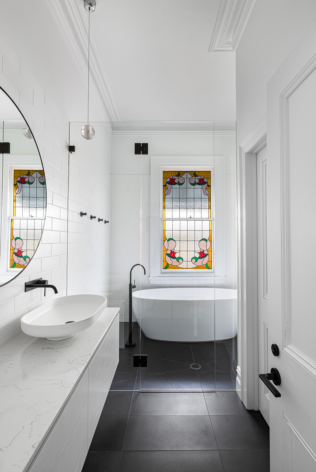 contemporary bathroom with white fixtures, black taps and frameless glass screen